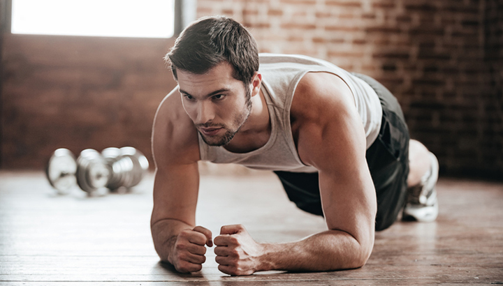 Confident muscled young man wearing sport wear and doing plank position while exercising on the floor in loft interior